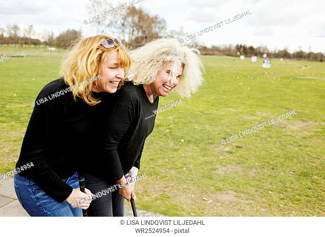 Cheerful female friends playing golf on weekend
