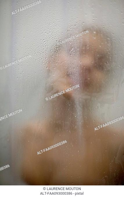 Woman behind wet glass, head and shoulders