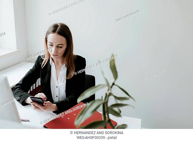 Young woman using cell phone at desk in office