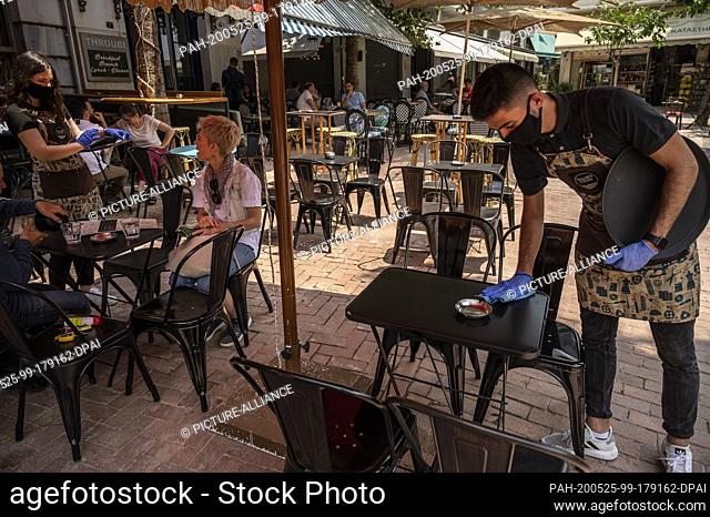 25 May 2020, Greece, Athen: A waiter with a face mask and disposable gloves wipes the table in a cafe. Greece relaxes measures imposed because of the Corona...