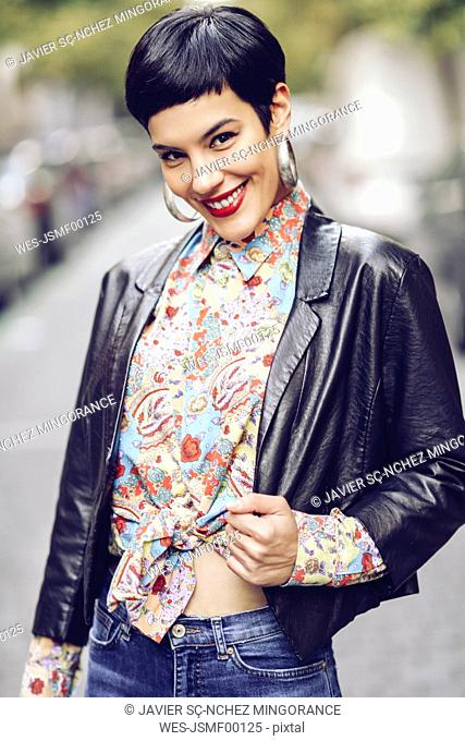 Portrait of fashionable young woman wearing patterned blouse and leather jacket