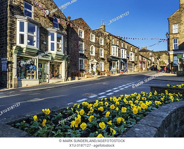 Winter pansies in flower and shops on the High Street at Pateley Bridge North Yorkshire England