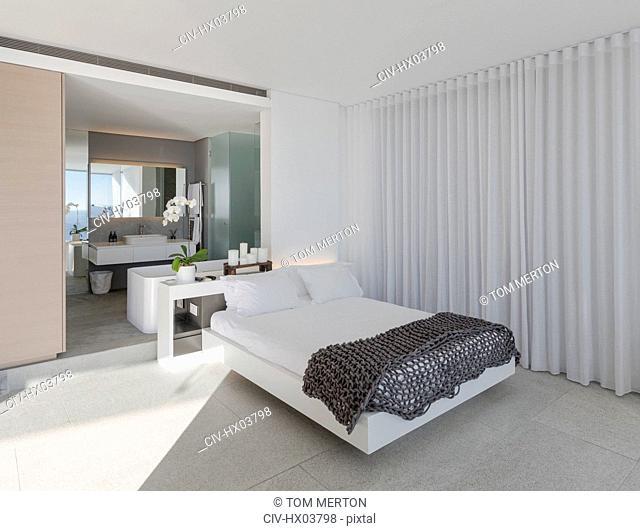 Bed in modern, luxury home showcase interior bedroom with en suite bathroom