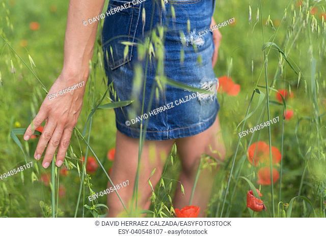 Woman enjoying a walk in a poppy field under the summer sun
