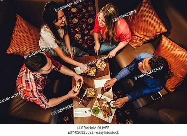 Overhead view of a group of friends having a meal at a restaurant. They are eating burgers and fish with chips