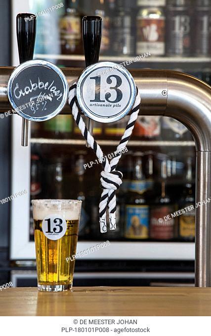 Hangman's rope, symbol of the city Ghent around tap and beer glass with pilsner / pilsener / pils 13, Belgian beer from Gent, East Flanders, Belgium