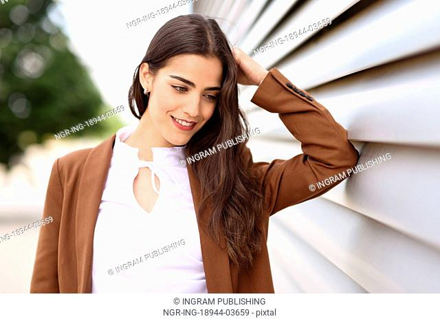 Young woman with nice wavy long hair. Beautiful girl wearing formal wear. Young female with brown jacket