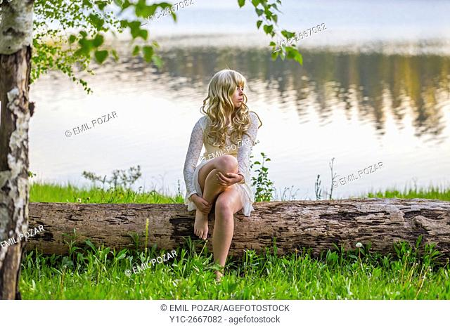 Teen girl sitting on tree trunk by calm lake
