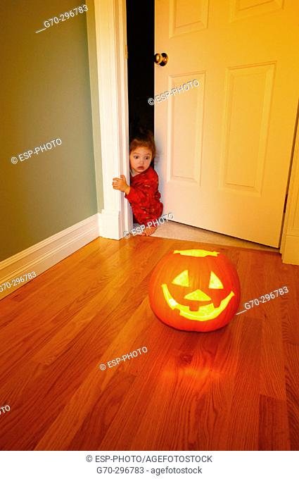 Halloween Jack-o'-lantern with scared little girl peeking around corner