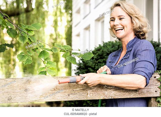 Mature woman playing with hosepipe in garden