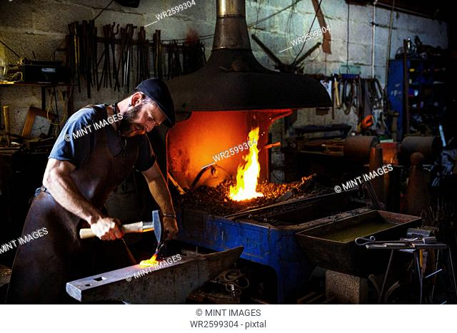 A blacksmith strikes a piece of red hot metal on an anvil with a hammer in a workshop