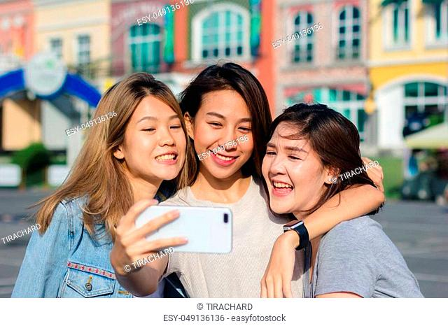 Attractive beautiful asian friends women using a smartphone. Happy young asian teenage at urban city while taking self portraits with her friends together with...