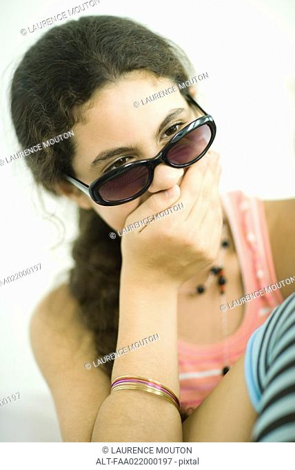 Preteen girl holding hand over mouth, looking over sunglasses, portrait