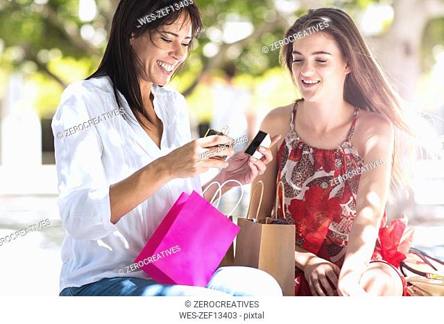 Happy mother and daughter with shopping bags in the city