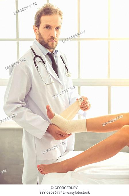 Handsome doctor bandaging woman's injured leg and looking at camera while working in his office