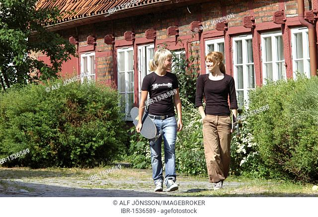 Two young girls, 15 years, walking in front of an old house, Ystad, Sweden, Europe