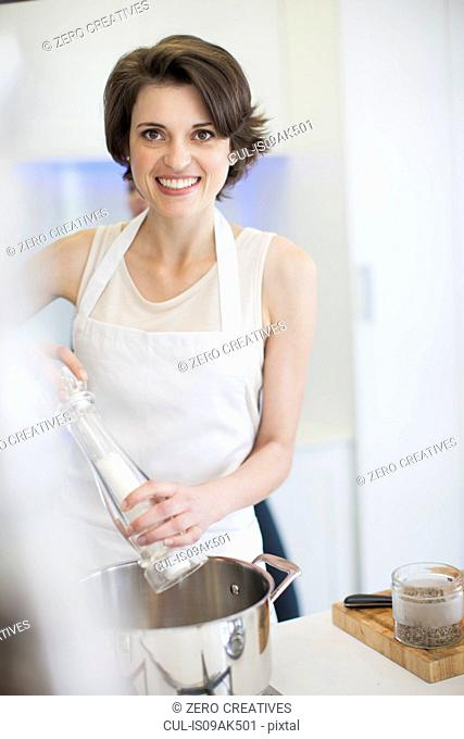 Portrait of young woman using salt mill whilst cooking in kitchen
