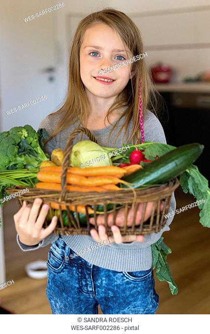 Portrait of smiling girl holding wickerbasket of fresh vegetables