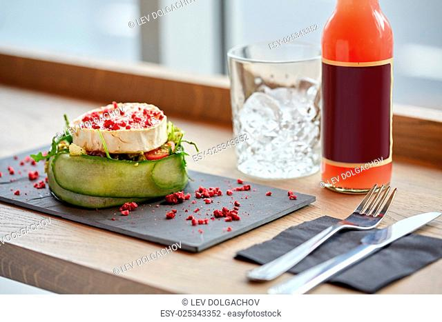 food, eating and object concept - goat cheese salad with vegetables, bottle of drink, glass with ice and cutlery at restaurant or cafe