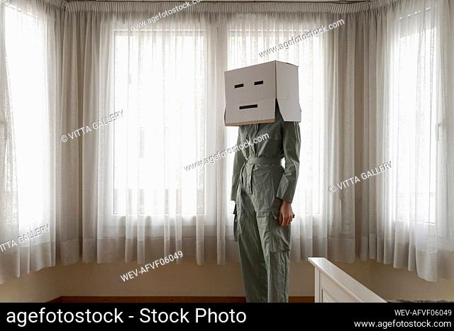 Woman wearing a cardbox on head with face