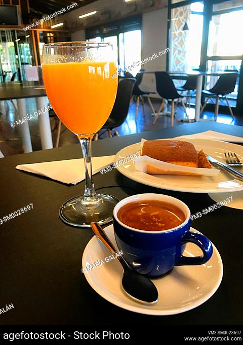 Cup of coffee, glass of orange juice and sobao pasiego in a cafeteria. Spain