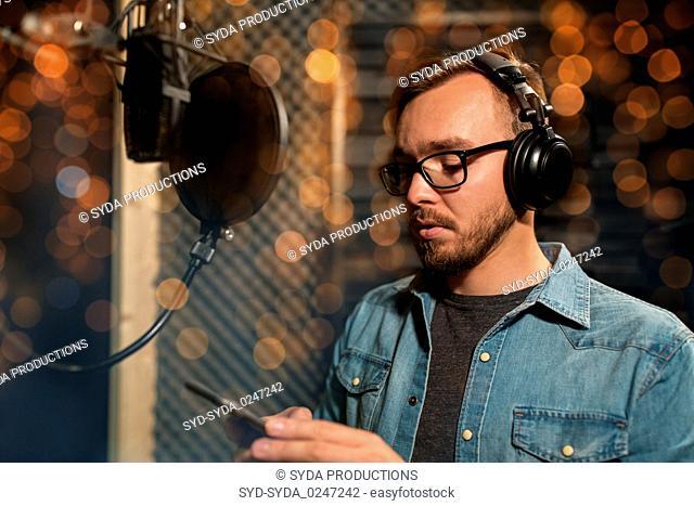 singer with headphones at music recording studio