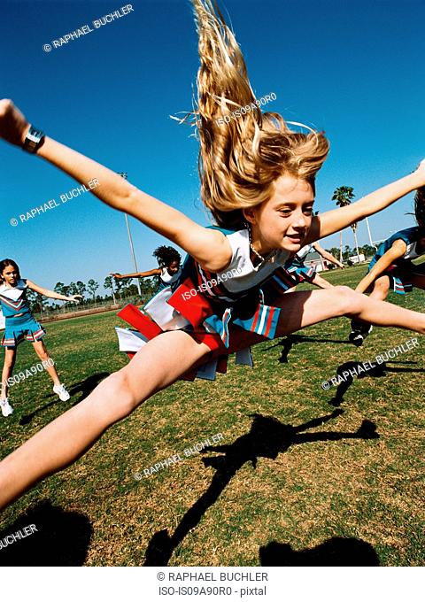 Young cheerleaders performing routine on football field
