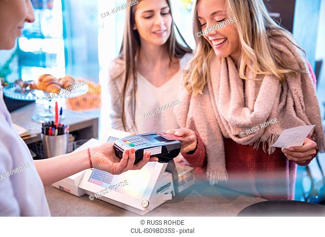Female friends standing at counter in cafe, paying using credit card