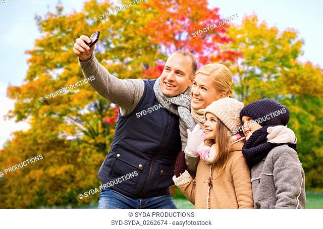 family taking selfie by smartphone in autumn park