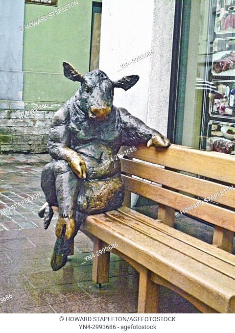 Bronze sculpture of a bull sitting of a street bench in Old Town, Tallinn, Estonia