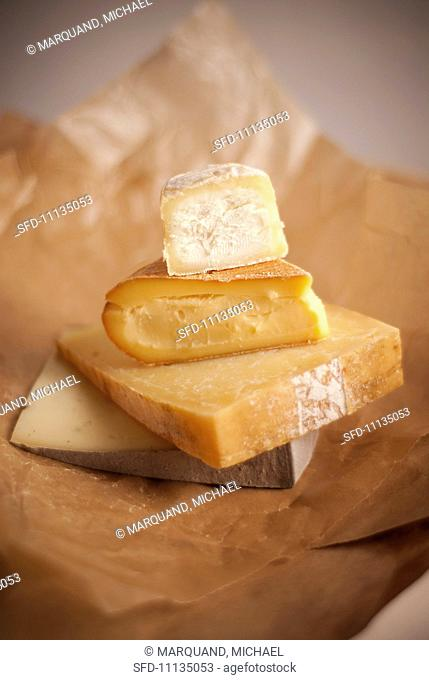 Four Assorted Cheeses Stacked on a Paper