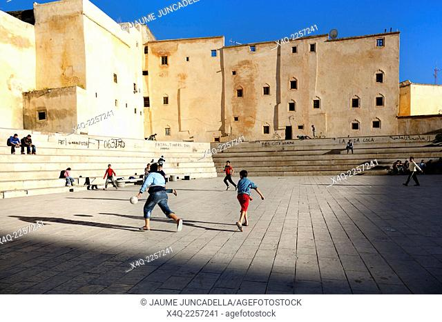 Fez, Morocco-April 25, 2014. Boys and children playing soccer in the square in one of the gates to enter to Medina of Fez in Marocco