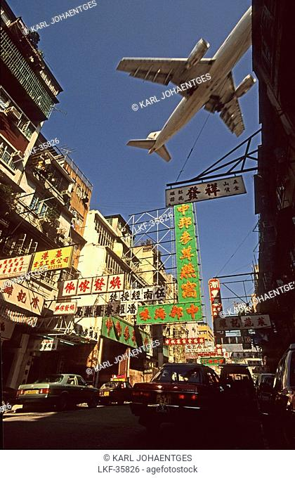 Aircraft flying above built-up area Kowloon, before opening airport on Lantau, Hong Kong, China
