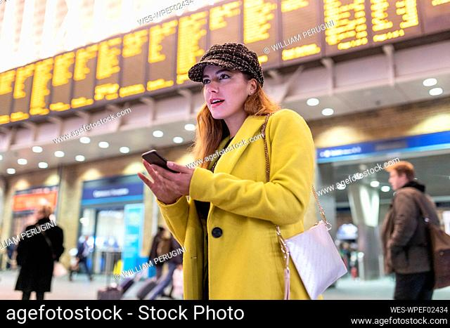 Woman at train station checking her smartphone