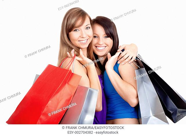 two happy young girls with shopping bags smiling - isolated on white