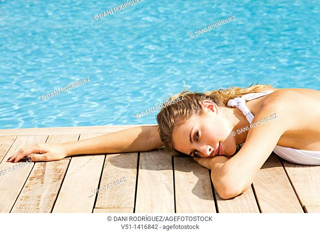 Blonde beautiful woman resting and lying down by the pool