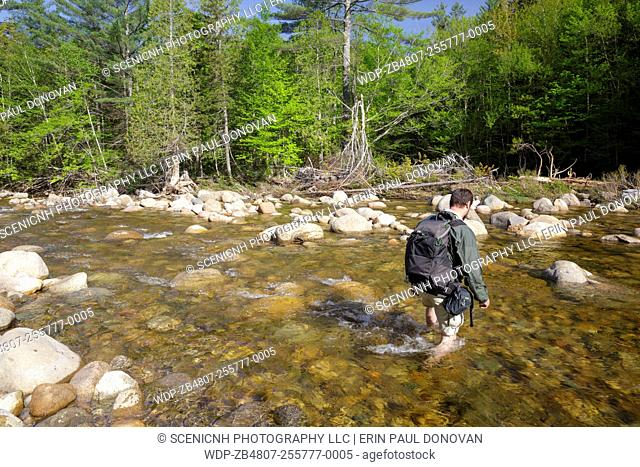 Hiker crossing the East Branch of the Pemigewasset River in the Pemigewasset Wilderness of Lincoln, New Hampshire USA