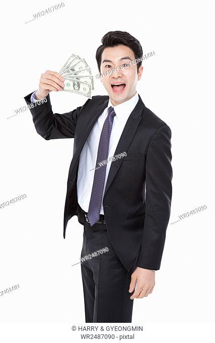 Smiling business man in suit showing dollar bills