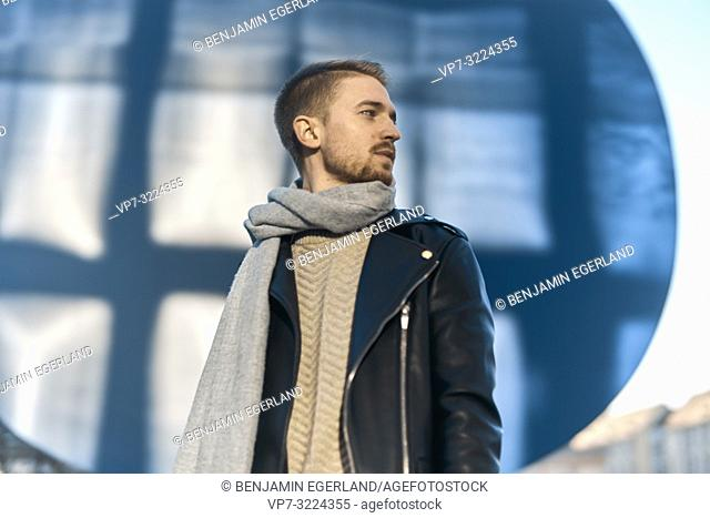 fashionable man wearing winter clothes, scarf, looking to side, in Munich, Germany