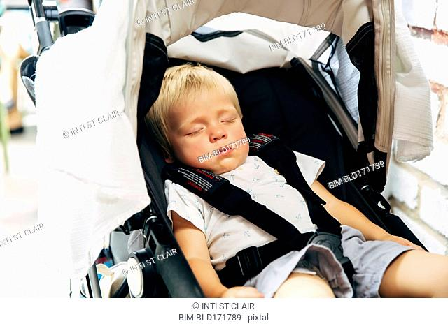 Mixed race boy sleeping in stroller