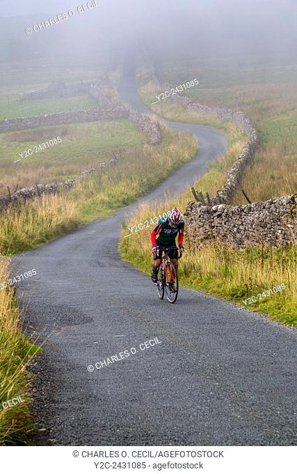 UK, England. Rider Cycling in the Yorkshire Dales in Autumn