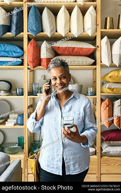 Woman talking on phone and looking direct while smiling and shopping