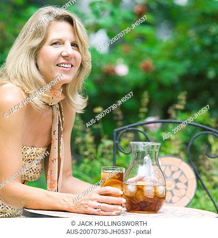 Portrait of a mature woman sitting at a table and drinking ice tea