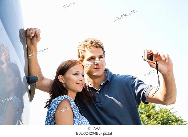 young couple taking picture of themselves with digital camera
