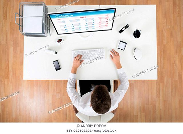 High Angle View Of Young Businessman Looking At Calendar On Computer At Desk In Office