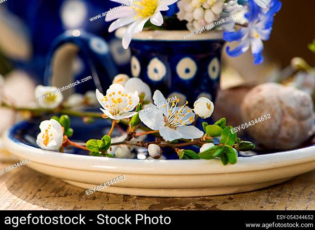 Little spring flowers in a eggcup and other decoration