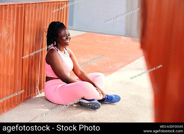 Cheerful plus size woman looking away while sitting on footpath
