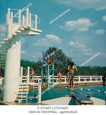 United States servicemen swimming in a pool, one soldier sits in the lifeguard chair while another is on the diving board