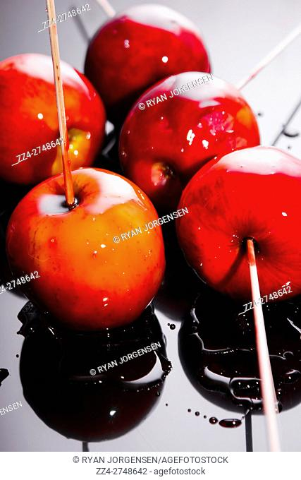 Sticky red toffee apple childhood treat with five ripe fresh apples dipped in syrup hardening on a baking tray to give the traditional crackly brittle candy...