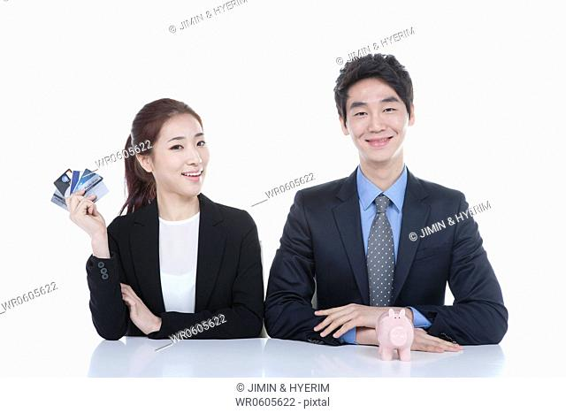 A man and woman with piggy bank and credit card